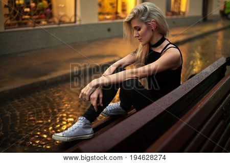 Young woman sits on wet bench on city street in evening in rain. In background there are lights of night city and reflections on wet pavement.
