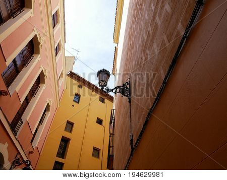 Low angle view of yellow and orange color residential building taken on a street in Madrid Spain.