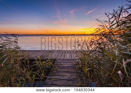 Sunset Over Wooden Boardwalk On The Shore Of A Lake