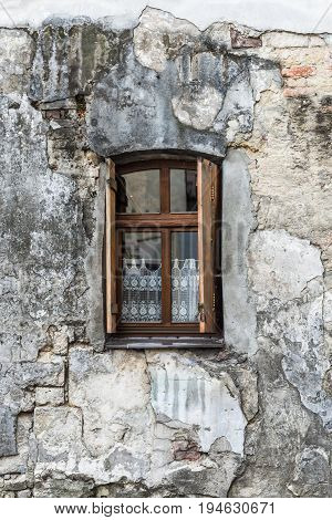 Old window on cracked wall in an ancient stone building