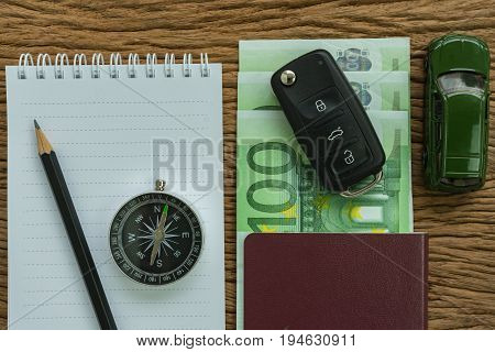 car key on euro banknotes passport compass pencil paper note and miniature car on wood table as travel planning road trip concept.