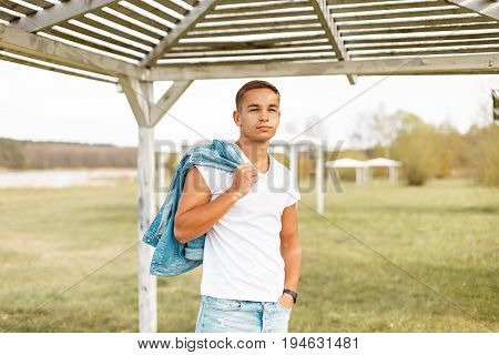 Beautiful Fashionable Man In A White T-shirt With A Jeans Near A Wooden Canopy