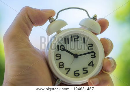 woman hand holding a white alarm clock as business or time countdown concept in summer sun shine.