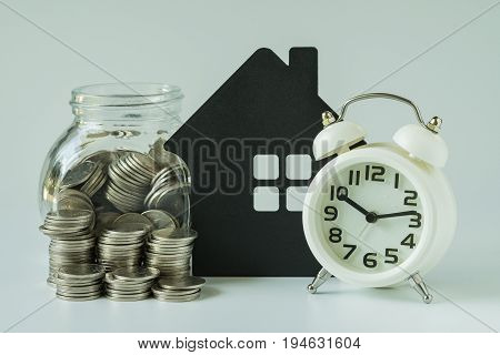 financial saving or mortgage concept with stack of coins and coins in glass pot with paper house on white background.