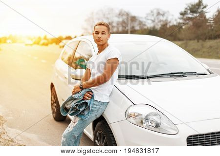 Handsome Young Man In A White Tank Top Near The Car At Sunset. Traveling On The Roads