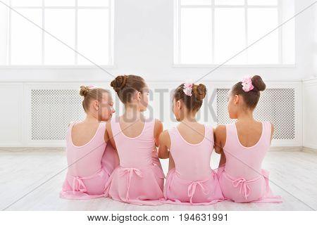 Little ballerinas talking in ballet studio. Group of girls having break in practice, sitting on floor, back view. Classical dance school