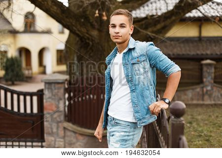 Stylish Young Handsome Man In Denim Jacket And Jeans In The Yard