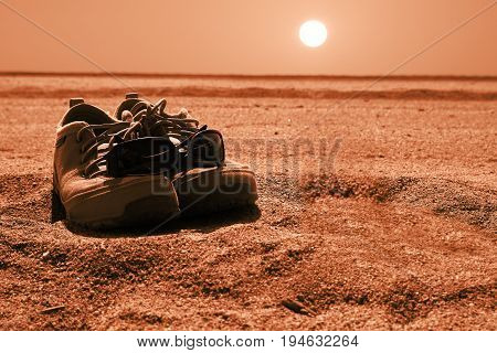 Boots and sun glasses on the desert sand at sunset during a journey. Explorer symbol and an empty copy space for Editor's text.
