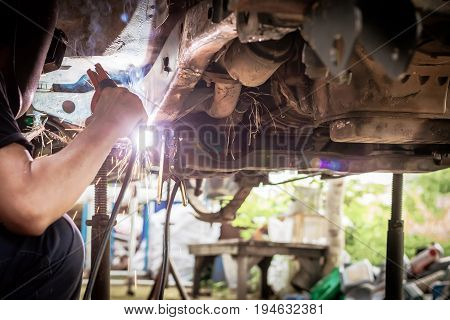 Technician are welding assembly steel under the car in automotive industrial factory with protection mask-Automotive industry and garage concepts.