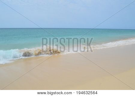 Perfectly clear beach and sky with crashing waves