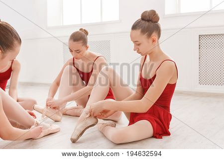 Young ballerinas put on pointe shoes in studio. Group of graceful pretty young girls preparing for practicing during ballet class. Classical dance school