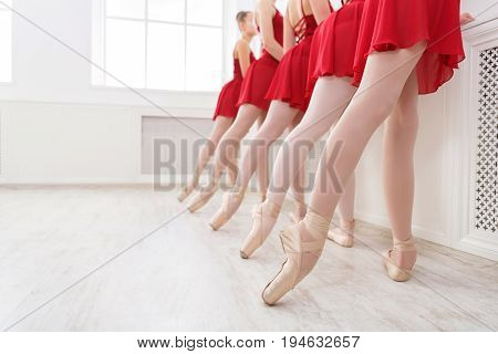 Ballet background, young ballerinas training. Female dancers legs in pointe shoes, making exercises. Classical dance school, copy space