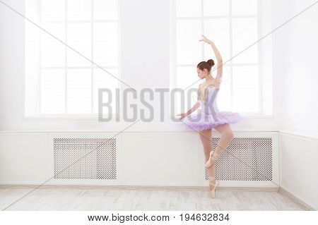 Ballet student exercising in ballet costume, standing on her toes. Young teenager ballerina practicing classical dance pas in studio before performance