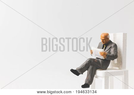 Miniature People Business Concept Sitting On Chair With A Space For Text