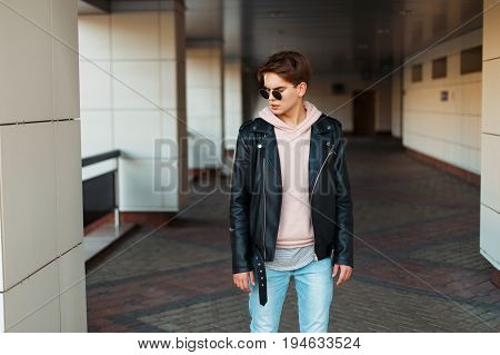 Handsome Young Man In Aviator Sunglasses In Black Leather Jacket And Pink Sweatshirt Posing Near Bui