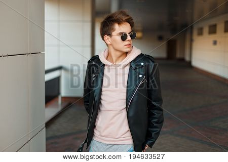 Young Handsome Man In Aviator Sunglasses In A Black Leather Jacket And A Pink Sweatshirt Near A Mode