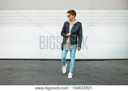 Handsome Fashionable Young Man In A Leather Black Jacket And White Sneakers Near A White Metal Gate
