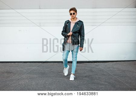 Handsome Young Model Of A Man With Sunglasses In A Black Leather Jacket, A Pink Sweatshirt, Blue Jea