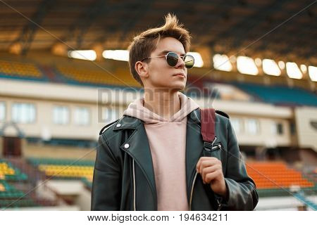 Beautiful Portrait Of A Young Sports Man With Sunglasses In A Black Jacket With A Backpack At The St