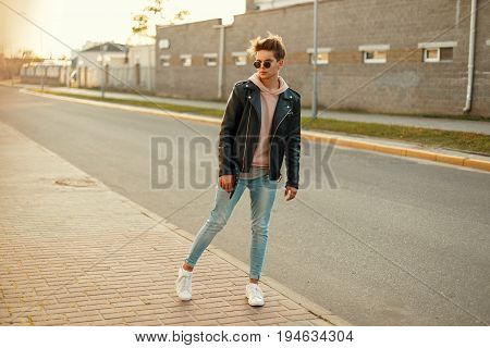 Young Model Guy In A Black Leather Jacket, A Pink Sweatshirt, Jeans And White Sneakers Posing On The