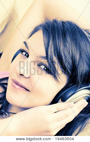 Portrait of Young Girl enjoying listening music in headphones - cross-processed poster