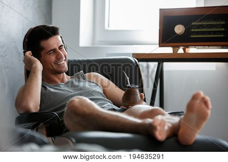 Young happy man drinking yerba mate and listening to music