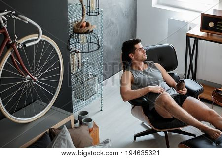 Handsome muscular man relaxing in his bedroom with yerba mate
