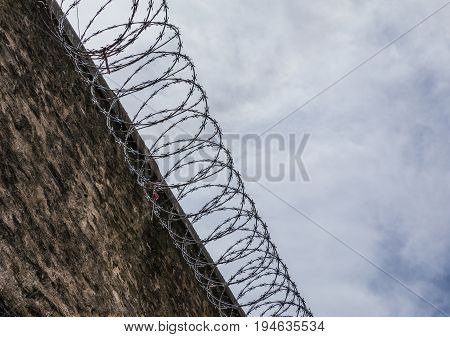 Concrete wall of the prison with cutting steel barbed wire