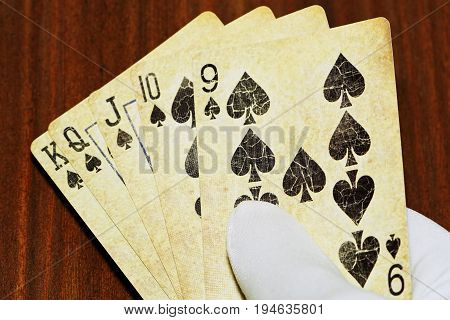 Straight flush poker combination in male hand in glove