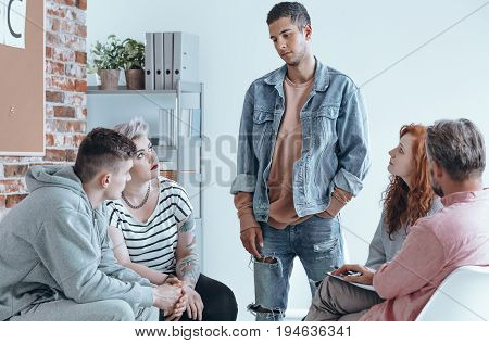 Teenager speaking to a group of contemporaries on therapy session