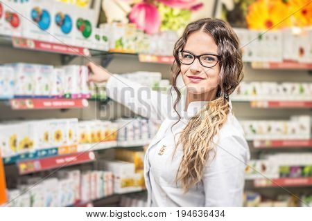 Young female smiling pharmacist standing in pharmacy