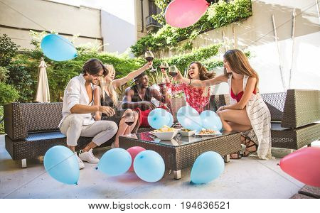 Multiethnic group of friends making party in a lounge bar - Cheerful young adults having fun and celebrating in a backyard garden with swimming pool