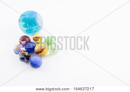 Balls of different colors and a larger ball on a white background.