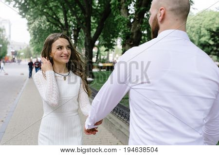 Young, Beautiful Bride And Groom Walking Along The Street In The City