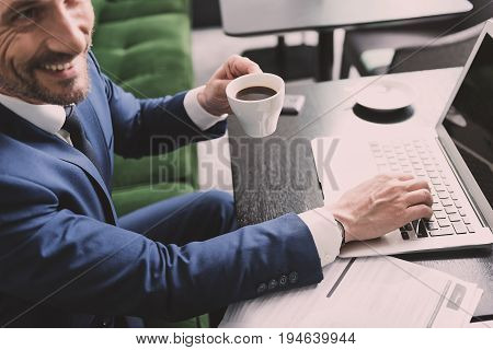 Top view of excited man in suit drinking coffee in cafe. He is using modern computer and laughing while sitting at desk