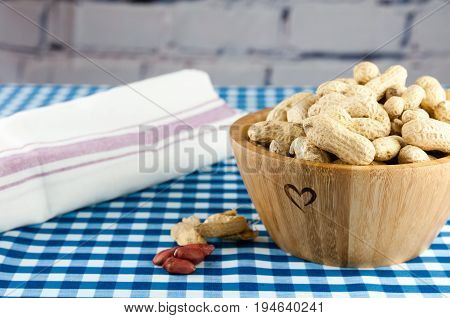unshelled monkey nuts in a wooden bowl with a heart symbol on the side