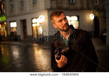 Young male photographer stands on city street in evening. In background there are night city lights. Self-portrait