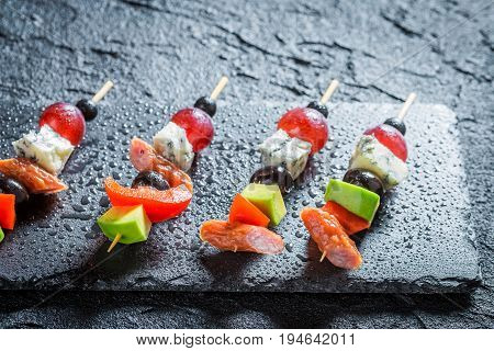 Tasty Finger Food With Vegetables And Herbs On Black Table