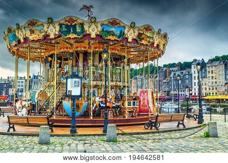 Spectacular retro carousel in the city. Merry-go-round with horses and landau in the famous French harbour Honfleur Normandy France Europe