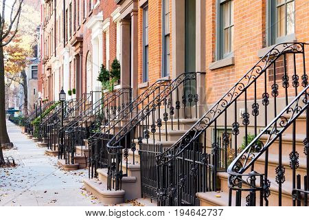 Row of old historic brownstone buildings along an empty sidewalk block in the Greenwich Village neighborhood of Manhattan New York City NYC