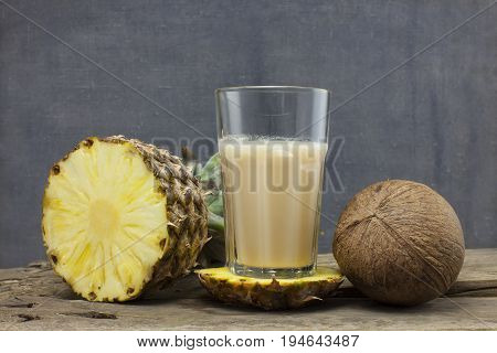 organic smoothie pineapple and coconut juice glass on wooden background
