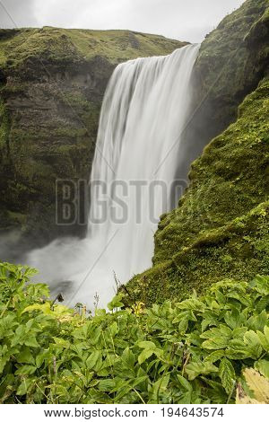 Waterfall shot with a long exposure method to generate motion blur effect with a rock overhanging a cliff fall