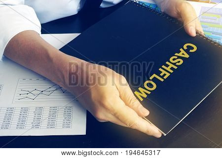 Businessman is holding book with name cashflow.