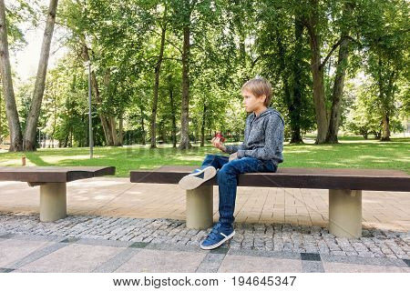Boy playing with red spinner alone outdoors