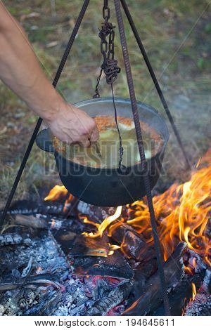 Cooking soup on fire.Tourists prepare a soup in the woods.