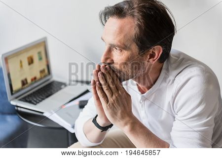 Pensive senior man is experiencing problems in business. He is sitting near working laptop and looking sideways with sadness. Portrait