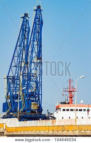 Big cargo ship in sea port terminal with cranes in Balchik Bulgaria.