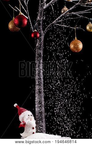 Toy Father Christmas under a Christmas tree with snow falling on him. Decorations and balls hang from the tree. Festive scene on a black background