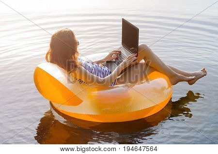 Business Woman Working On A Laptop In An Inflatable Ring In The Water, A Copy Of The Free Space. Wor