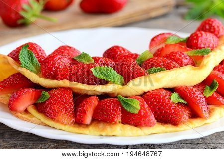 Homemade eggs omelet stuffed with fresh strawberries and decorated with mint leaves. Delicious and healthy breakfast omelet idea for whole family. Closeup